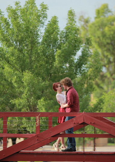 Young couple kissing on a bridge engagement photography