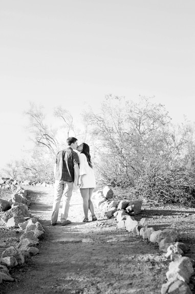Young couple engagement photography papago park walking and kissing