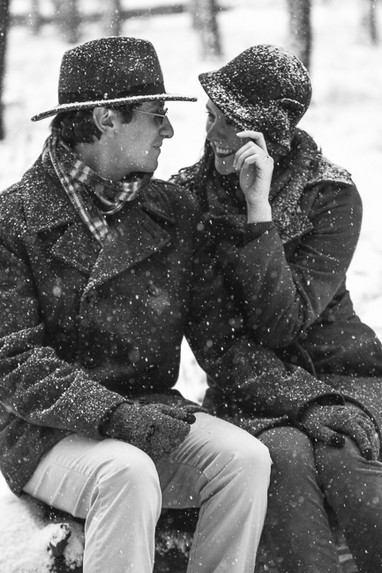 Beautiful young couple in snowy forest for engagement photos
