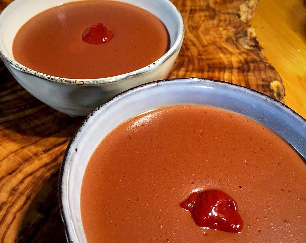 Zwei Schälchen mit glutunfreiem und milchfreiem Pudding mit einem Kleks dunkelroter Himbeersoße in der Mitte