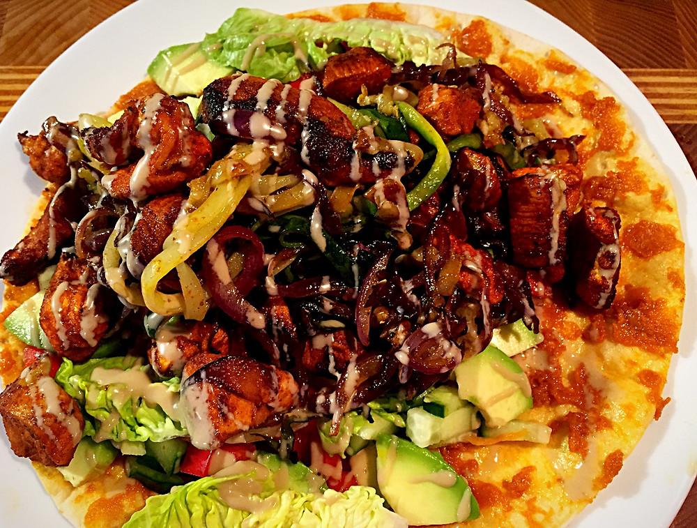 Ein etwas überfüllter Wrap mit  Salat, Zucchini-Spagetti, Zwiebel, Avocado, Soße und Hühnchen