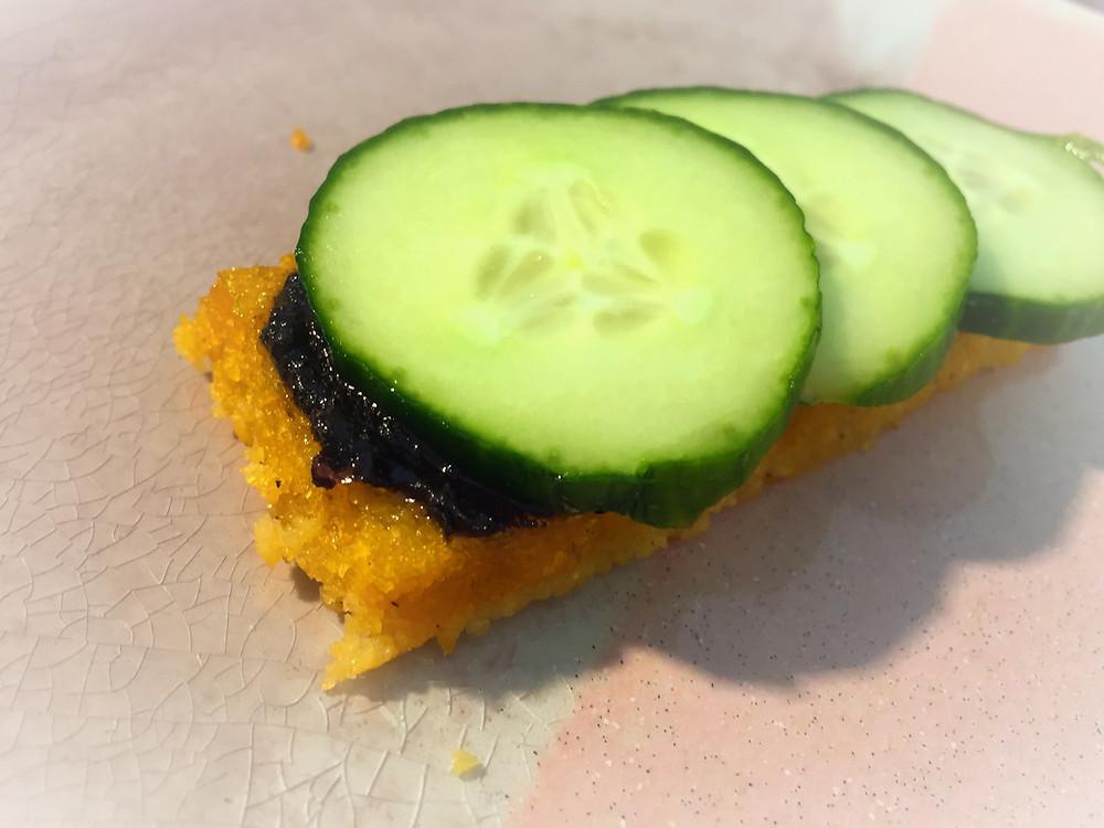 Eine Scheibe Polenta mit schwarzer Paste bestrichen und grünen Gurken oben auf