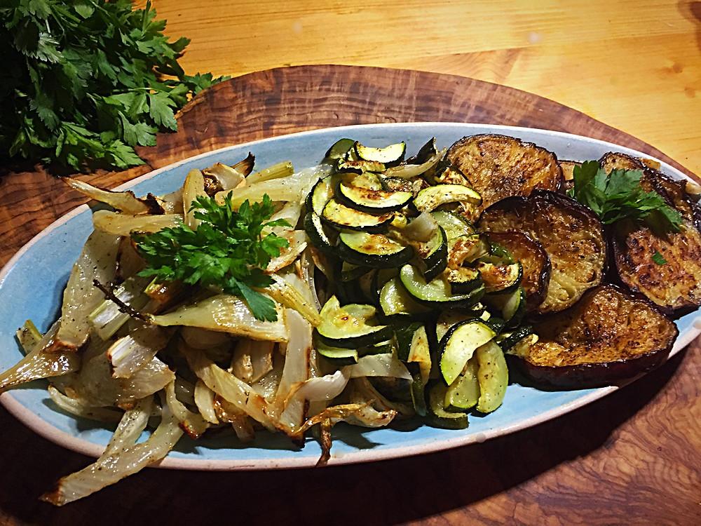 Drei Gemüse auf einem Teller - gerösteter Fenchel, Zucchini und Auberginen mit Petersilie dekoriert