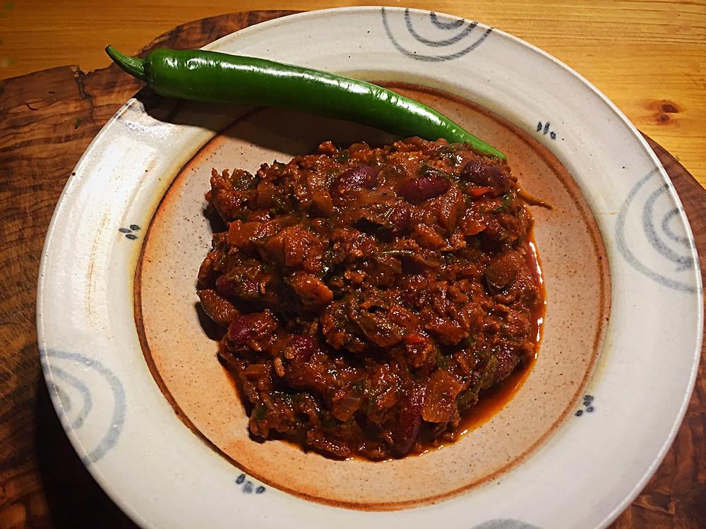Schöner Teller mit Chili-Eintopf und einer grünen Chili als Dekoration
