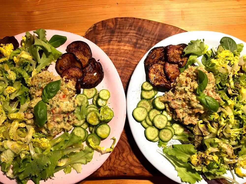 Zwei teller mit gemischtem Salat, Auberginenscheiben und dem Krabbensalat in der Mitte