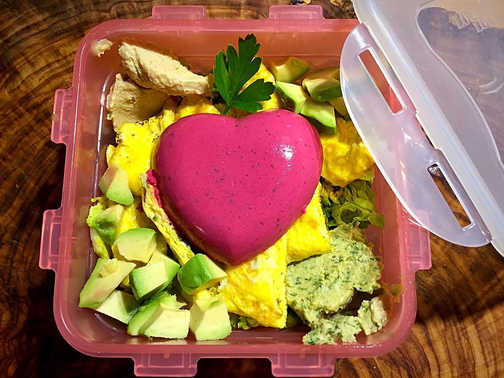 Gemischter Salat mit Ei und Tunfischpastete in Herzform in einer rosa Lunchbox