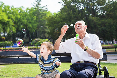 grandfather blowing soap bubbles to gran