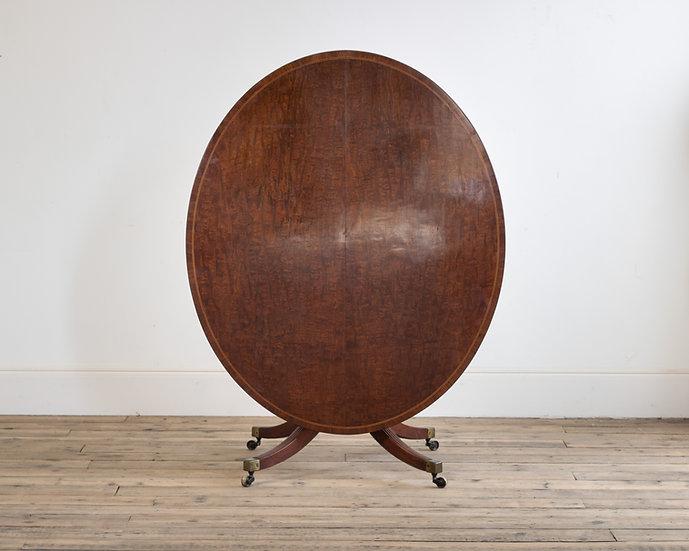 A Regency 'plum-pudding' mahogany oval breakfast table