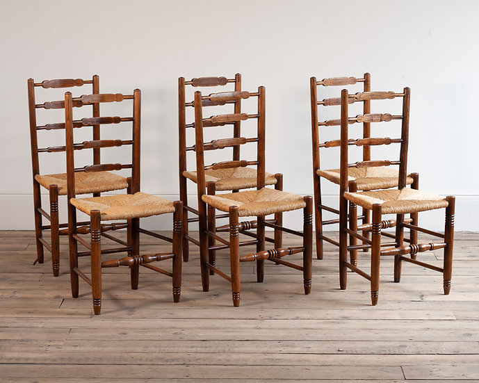 A set of six ladder-back rush seated dining chairs