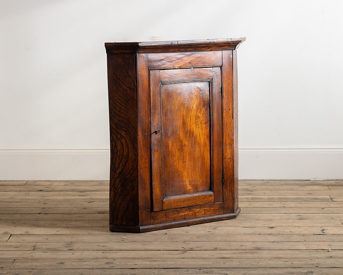 An 18th century elm corner cupboard