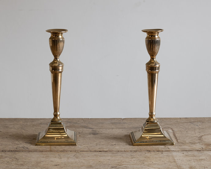 A pair of late 18th century brass candle sticks