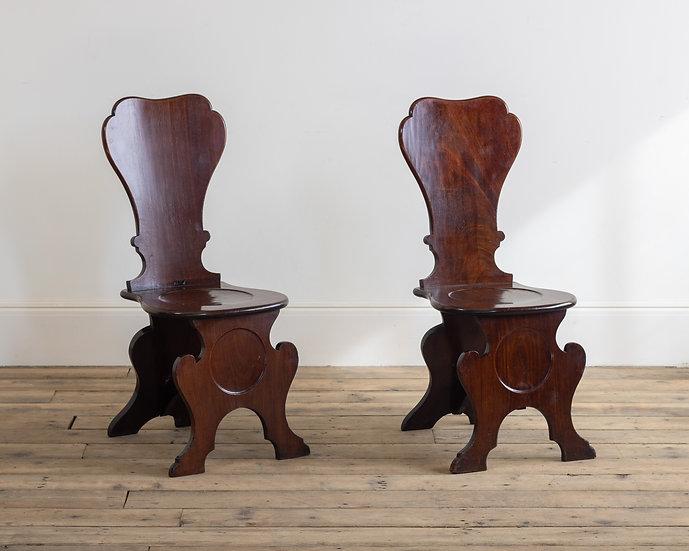A pair of George II mahogany hall chairs