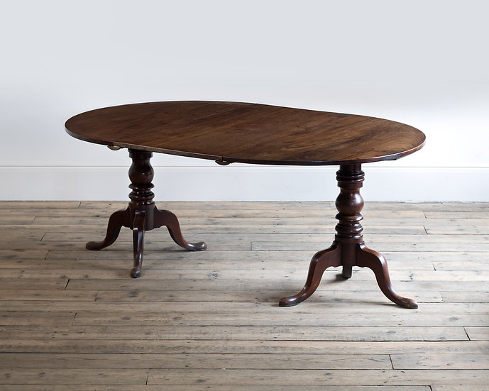A George III twin-pedestal mahogany dining table