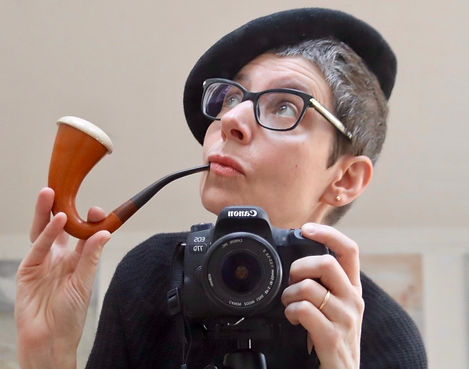 a portrait of artist Sonia Boué She is holding a camera and posing with a pipe.