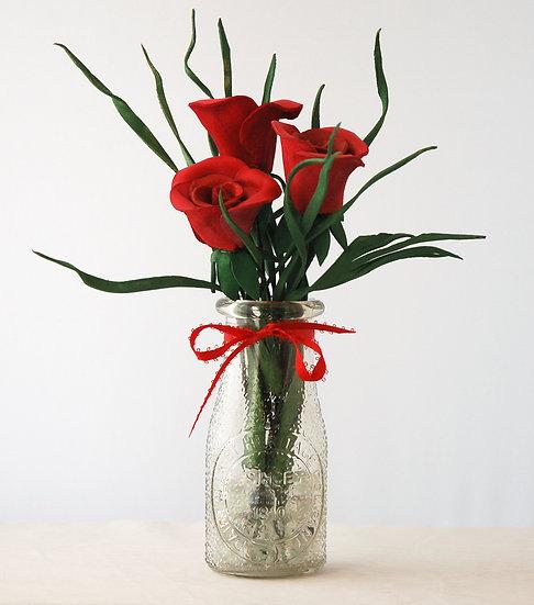 Three Red Roses in Clear Milk Jug Vase