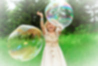 Pretty%20little%20girl%20is%20playing%20with%20big%20bubbles%20in%20a%20park._edited.jpg