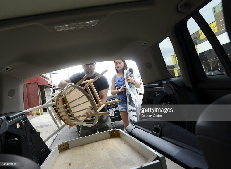 Cheap Chic owner and president Chris Silvera helps a customer load furniture into her car