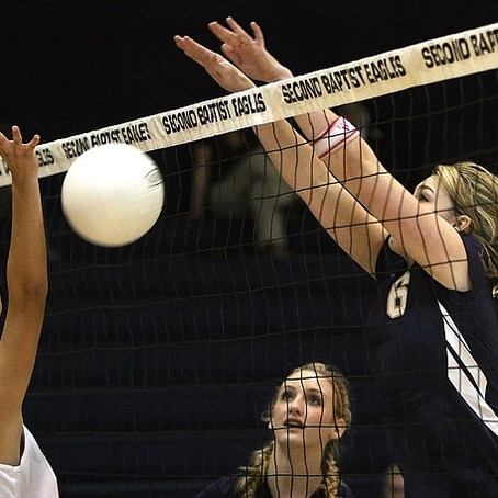 Can the ball hit the net on a serve in volleyball?