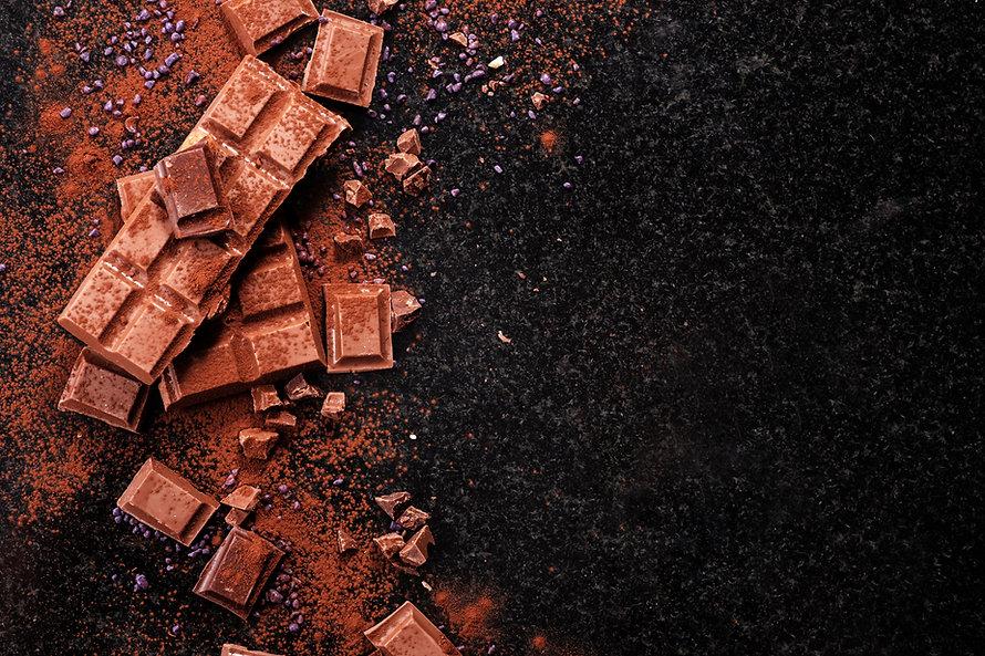 Broken chocolate pieces and cocoa powder