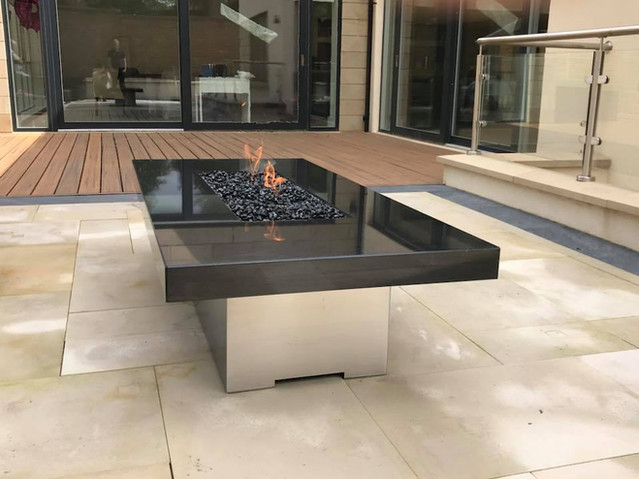 Polished black granite and stainless steel fire table.