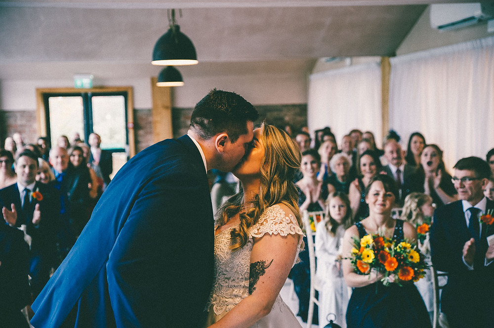 Rustic barn at willerby wedding ceremony bride and groom first kiss