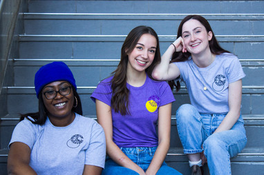 """Three club members sitting on stairs wearing shirts that say """"feminism is for everyone"""""""
