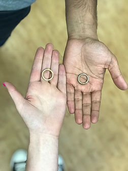 Two hands holding finished handmade wedding bands