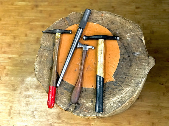 Jeweler's tools on wood stump: mandrel and hammers
