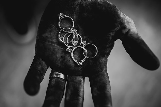 Black & white image of jeweler hand covered in polishing compound contrasting with handful of rings