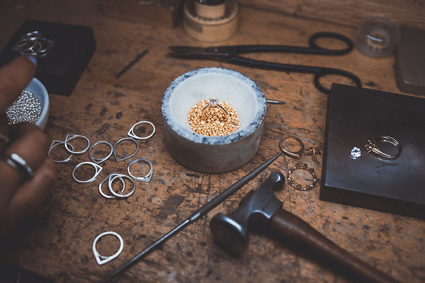 Gold casting grains in crucible with black & white diamond ring in center surrounded by tools
