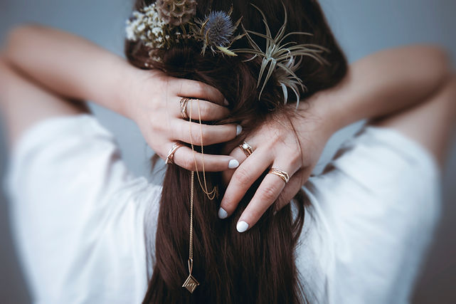 Woman with flowers in hair wearing stacking Apex bands holding diamond thaumatrope necklace