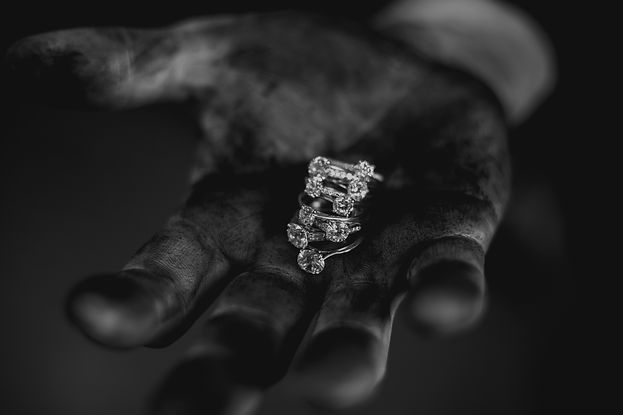 Black & white image of jeweler hand covered in polishing compound holding contrasting diamond rings