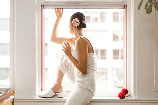 Woman in white with dahlia in hair sitting in city window wearing silver talon earrings and necklace