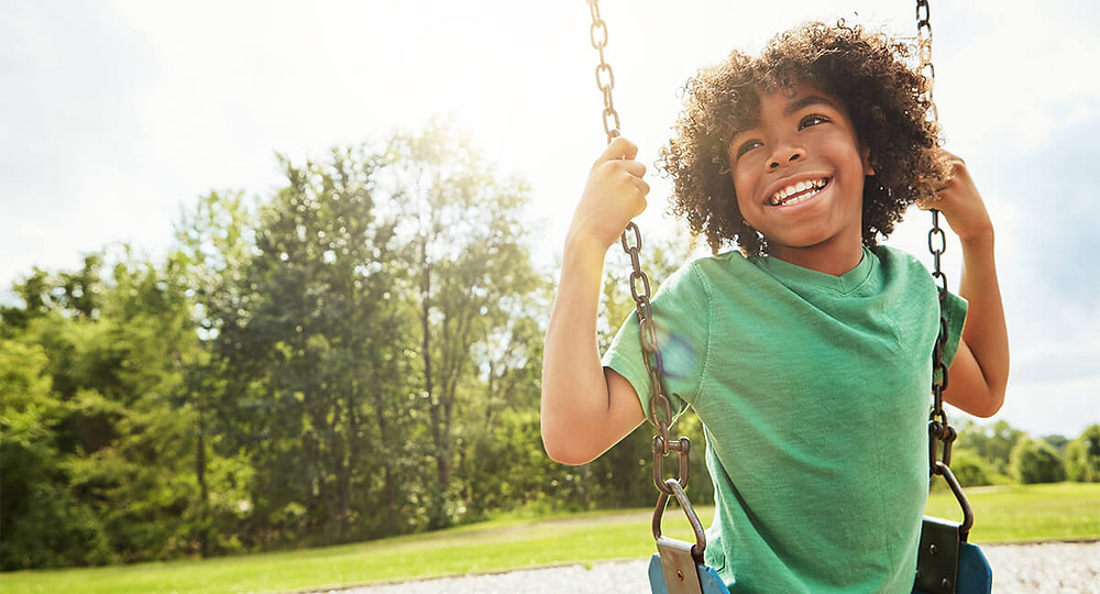 happy young boy playing on a swing
