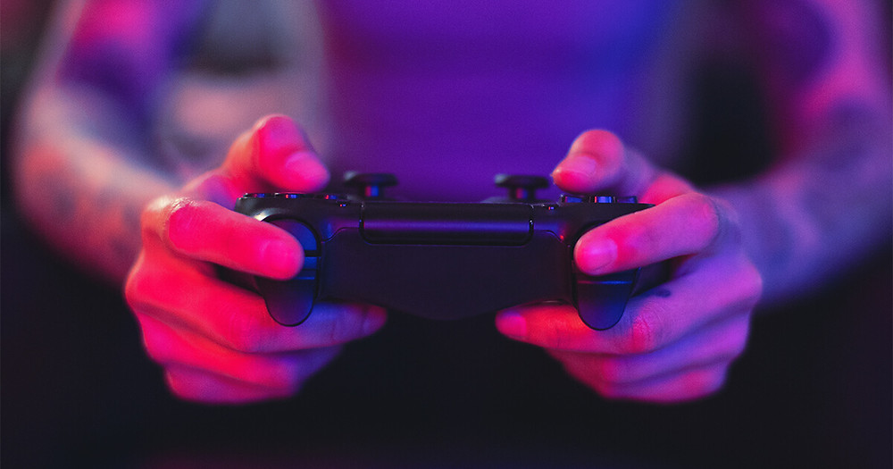 close up of hands holding video game controller