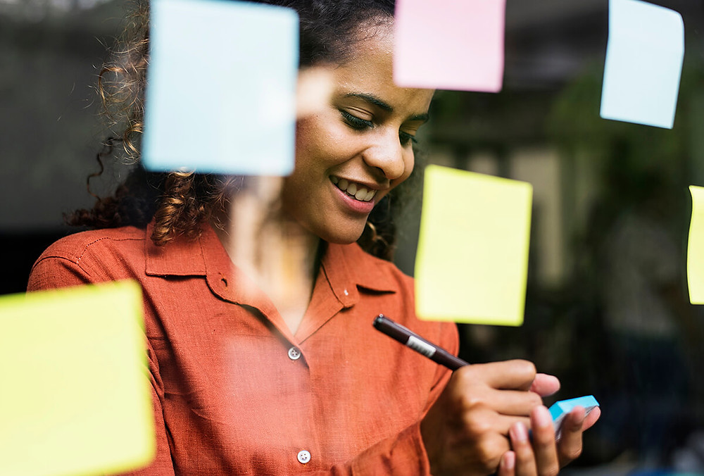 happy woman writing on sticky notes