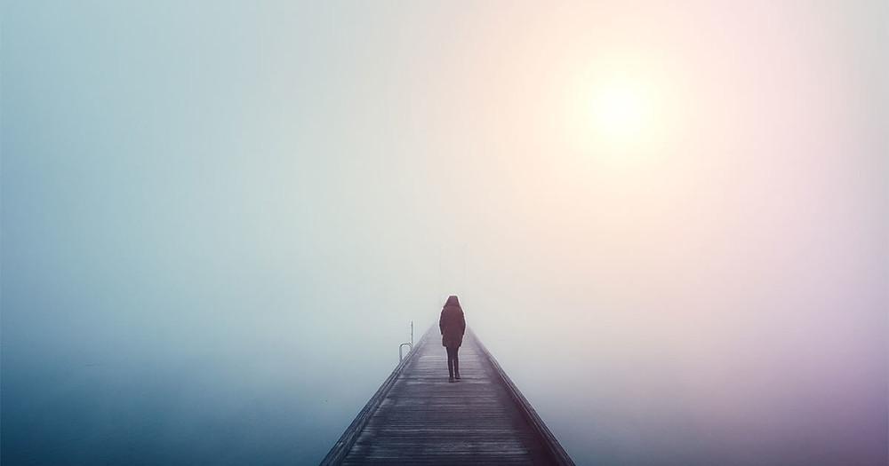 woman alone walking onto foggy dock