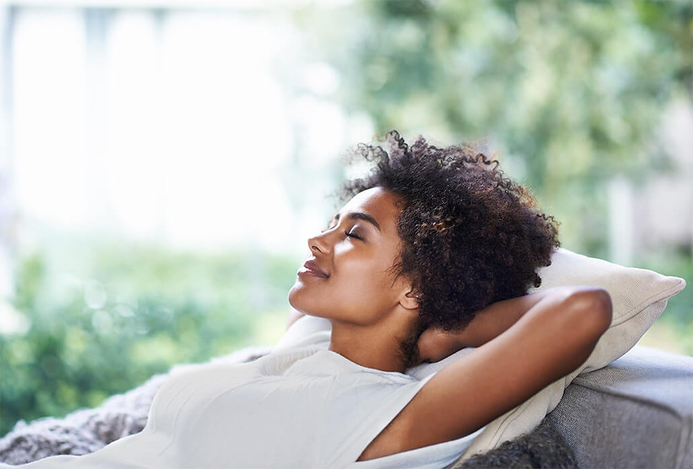 woman lying back with eyes closed smiling