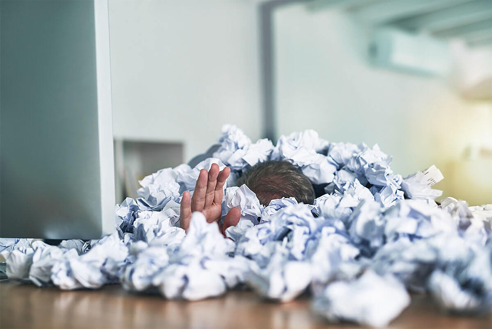 person buried in crumpled papers at desk