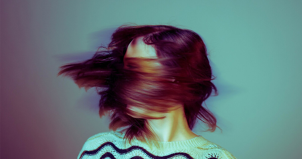 woman shaking head with hair covering her face