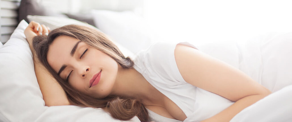 beautiful woman with closed eyes in bedroom in sunny morning at home