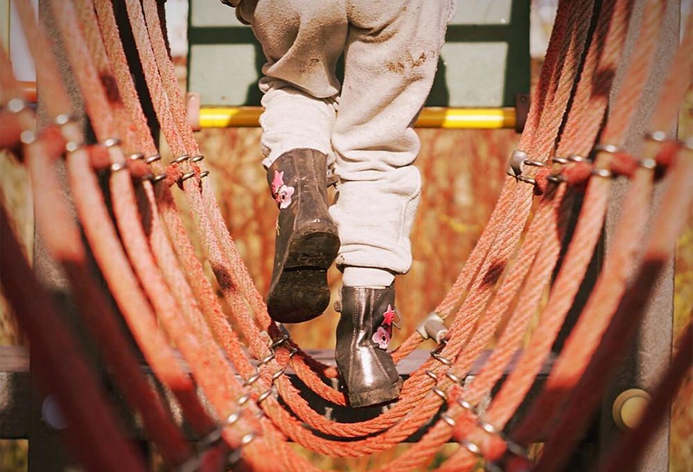 young girl's feet walking on rope bridge