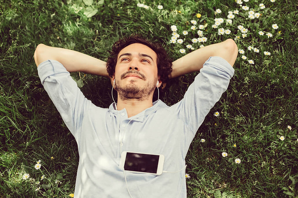 man laying in the grass with headphones connected to his phone as he stares up at the sky