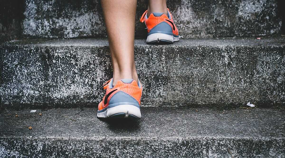 close up of athlete's feet going up stairs