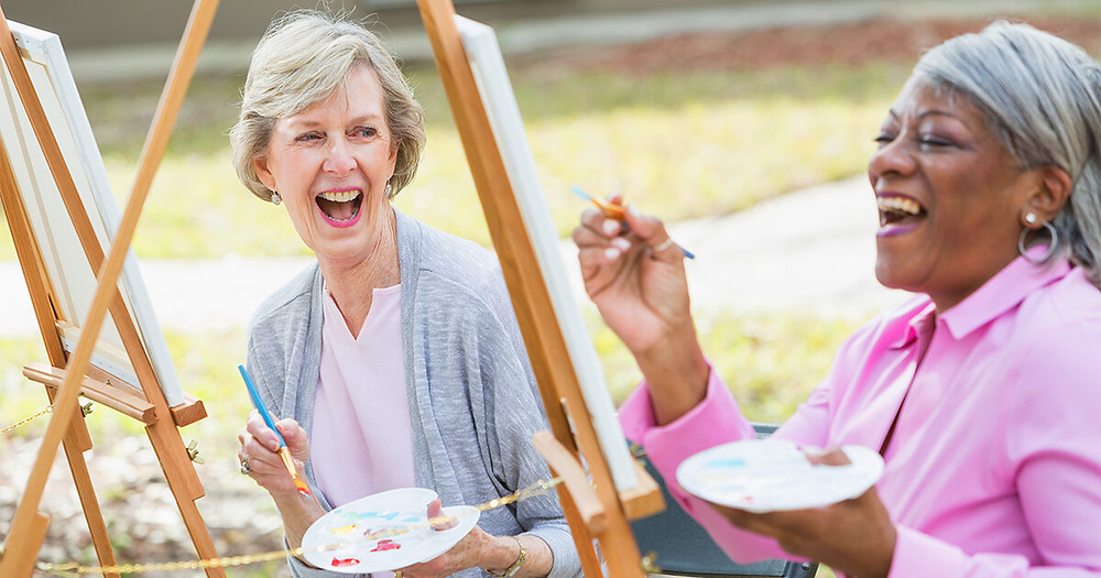 older women laughing and painting outside