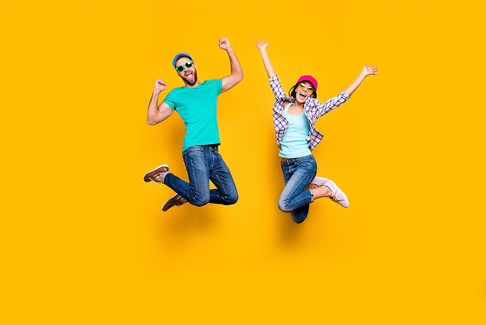 people jumping in front of yellow background