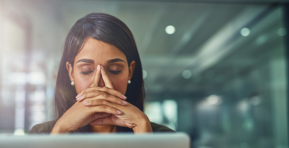 stressed woman with hands on face at computer