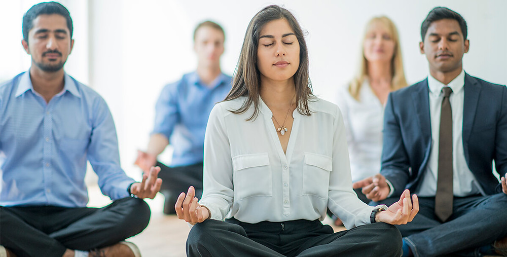 corporate workers meditating on the floor