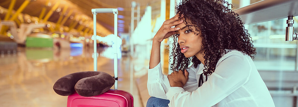 a woman stressed out while she is traveling and waiting at an airport