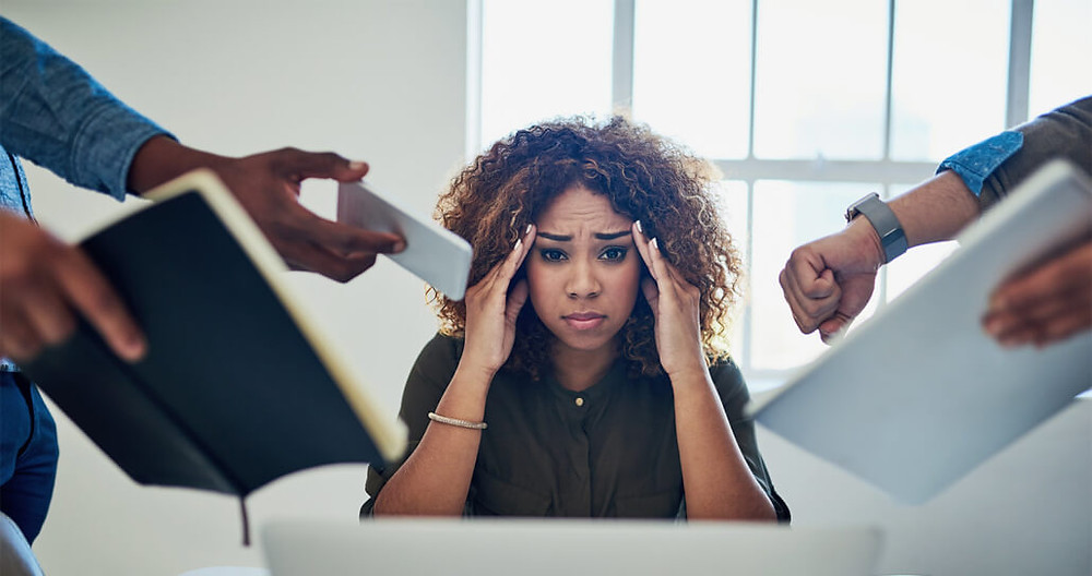 a woman stressed at work overwhelmed by coworkers